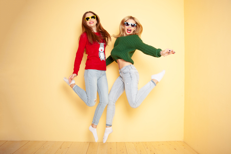 Photo pour Two funny beautiful hipster girls in sweaters and sunglasses. Concept winter and fashion.Jumping. Flying hairs - image libre de droit