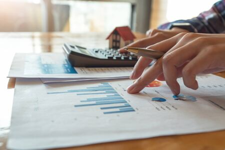Photo pour Woman press the calculator to calculating financial chart for investment to buying property - image libre de droit