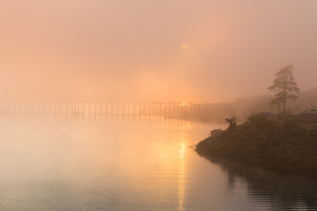 The sun behind fog at morning with the longest wood brigde in Thailand