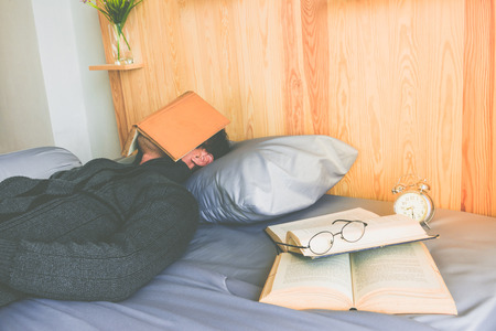 Asian man bored read book on bed after he tried reading a book in rest time