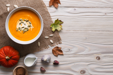 Traditional pumpkin soup with seeds and ingredients still life.