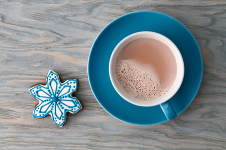 Photo pour A big cup of cocoa with a gingerbread snowflake-shaped candy on a blue wooden background, top view. - image libre de droit