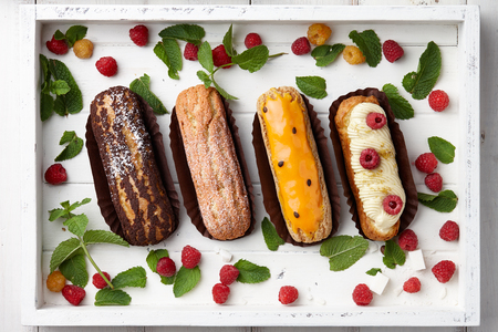 White wooden tray with french eclairs, raspberries and mint leaves, top view