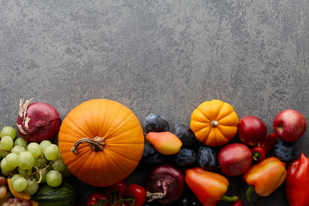 Autumn harvest concept. Seasonal fruits and vegetables on a stone tabletop, top viewの写真素材