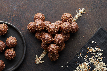 Photo pour Heart shape with arrow made from chocolate truffle candies with hazelnuts and nut crumb on brown textured background, top view - image libre de droit