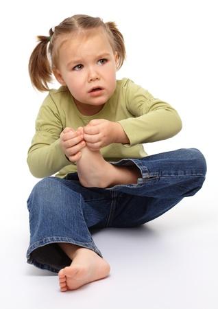 Little girl hurt her tiptoe, feeling pain, isolated over white