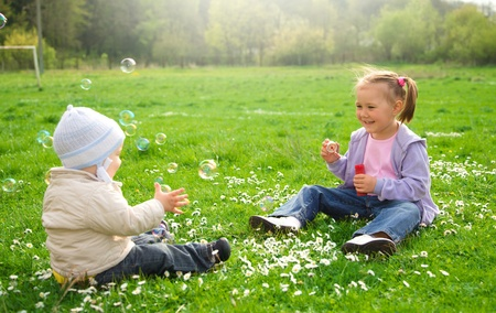 Two children are sitting on green meadow and blow a soap bubbles