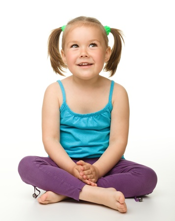 Portrait of a cute little girl sitting on floor, isolated over white