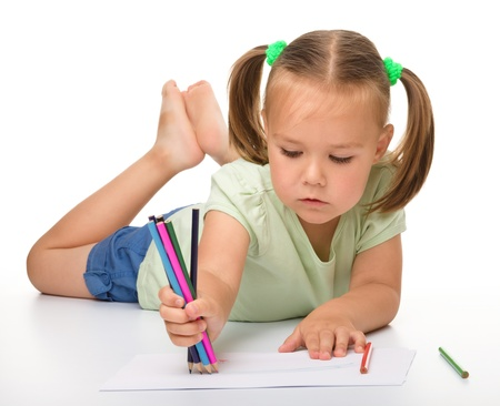Cute little girl is drawing while laying on the floor, isolated over white
