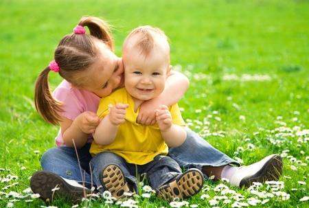 Foto de Two children are sitting on green meadow and smile - Imagen libre de derechos