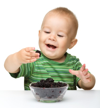 Cute cheerful little boy is eating blackberry, isolated over white