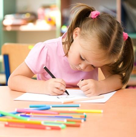 Cute little girl is drawing with felt-tip pen in preschool