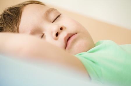 Portrait of a cute little boy sleeping in bed