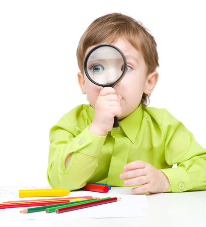 Cute little boy is looking through magnifier, isolated over white