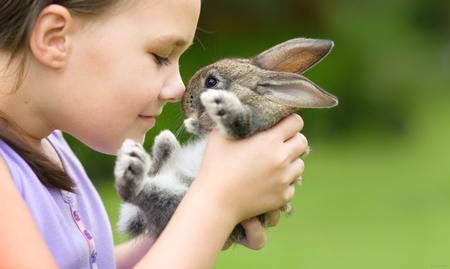 Foto de Girl is holding a cute little rabbit, outdoor shoot - Imagen libre de derechos