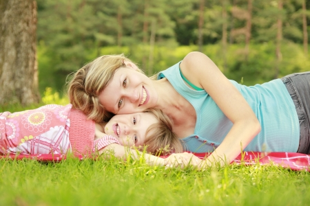Photo for a young mother and her little daughter playing on grass - Royalty Free Image