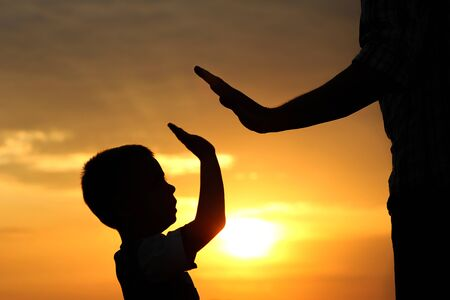 Photo for silhouette the parent holds the hand of a small child - Royalty Free Image
