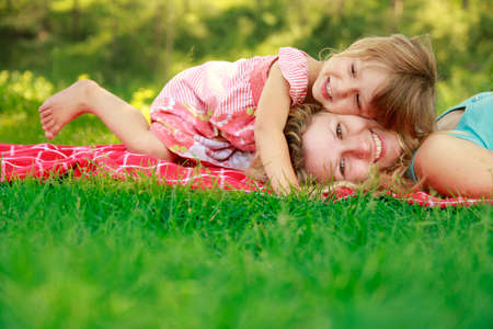 Foto per happy mother with baby in nature lying on the grass in the park - Immagine Royalty Free