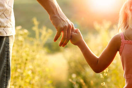 Photo pour hands of parent and child outdoors in the park - image libre de droit