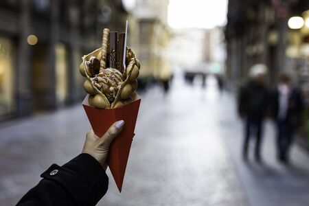 Photo pour Woman hand holding a bubble waffle with ice cream and candies on a red paper cone with blurred unrecognizable crowd on the background street in Europe - image libre de droit