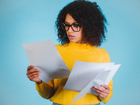 Photo pour Education and business concept - international student studying in college. Or modern african american businesswoman with afro hairstyle reading documents on blue background in studio. - image libre de droit