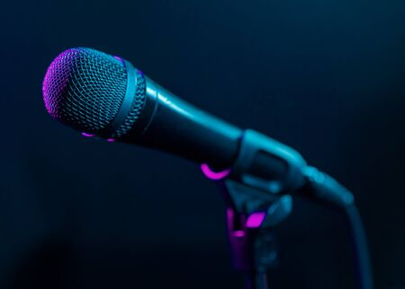 Photo pour Microphone on black background with colorful pink and turquoise light. Music, concert concept. - image libre de droit