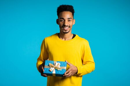 Foto de Handsome man in yellow wear holding gift box on blue studio background smiles to camera. Happy african american birthday guy. - Imagen libre de derechos