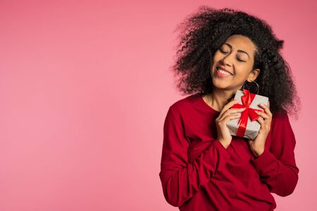 Foto de Beautiful african american woman received gift box with bow. She is happy and flattered by attention. Girl on studio background. - Imagen libre de derechos