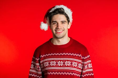 Foto de Portrait of happy young man in Santa hat and Christmas sweater isolated on red studio background. Winter holidays concept. - Imagen libre de derechos
