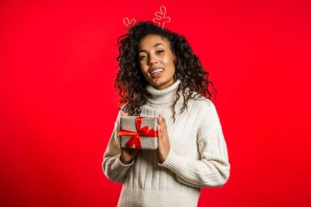 Young pretty african woman smiling and holding gift box on red studio background. Girl with curly hairstyle in white sweater. Christmas mood.