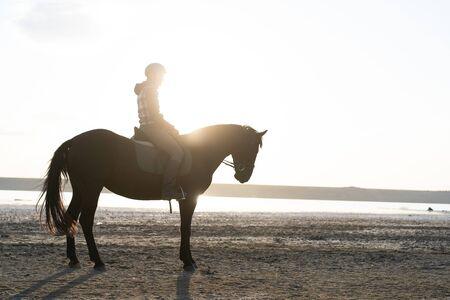 Foto de Woman rides horse on beautiful autumn nature landscape by river or lake. Sun flare, beautiful background. Concept of farm animals, training, horse racing - Imagen libre de derechos