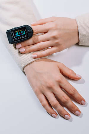 Photo pour Woman put on pulse oximeter on finger, check blood oxygen saturation. Monitoring heart rate at home during pandemic coronavirus covid-19 - image libre de droit