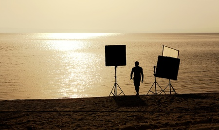 film crew setting up scene on a beach