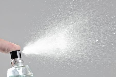 bottle spraying perfume against gray background