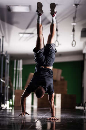 Photo for Muscular athlete standing and walking on hands upside down. - Royalty Free Image