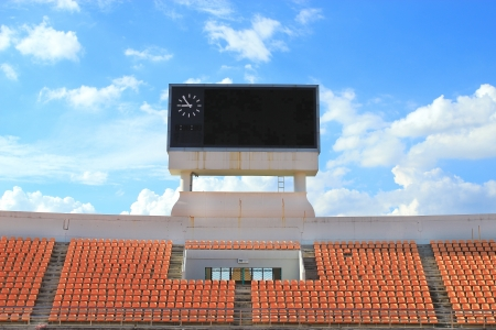 row of orange seats and score board ,blue sky and cloud backgroud