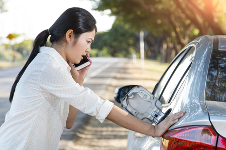 Car oil down and Young woman trying to calling for help on phone.