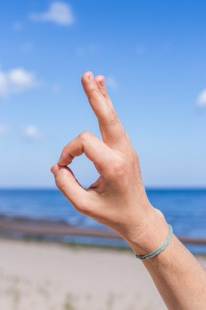 Female hand: fingers in the form of yogic gesture against the blue sea and sky.