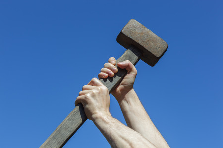 Construction worker holding a heavy hammer. Destroying something with strength and fury