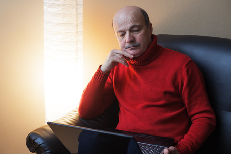 elderly man with a laptop sitting on the couch next to the lamp and something carefully studying