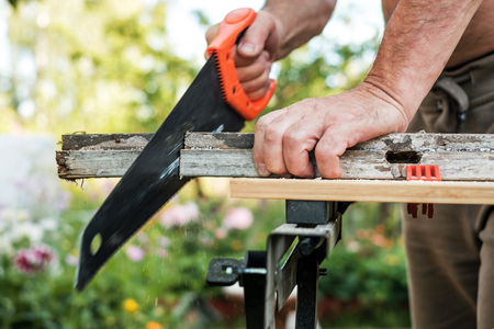 Photo pour Caucasian man working cutting plank with handsaw outdoor in summer. - image libre de droit