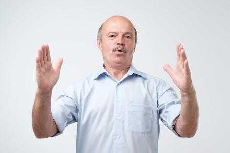 Photo pour Handsome mature man gesturing with hands showing big and large size sign, measure symbol. Measuring concept. - image libre de droit