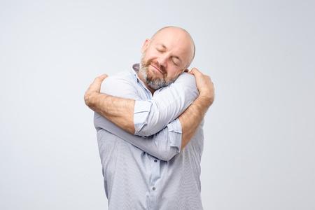 Foto de Closeup portrait of confident smiling man holding hugging himself isolated on grey wall background. Positive human emotion, facial expression. Love yourself concept - Imagen libre de derechos