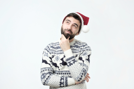 Photo for Hispanic man in red christmas cap thinking deeply about gifts, looking up, isolated on grey wall background. Planning new year party. - Royalty Free Image