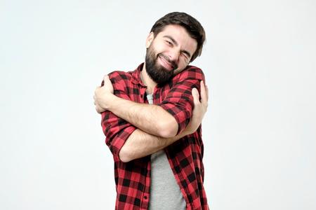 Foto de ortrait confident smiling man hugging himself. I am the best concept. Soft clothes after washing - Imagen libre de derechos