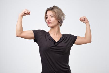 Foto de Happy young european woman showing her strong hand. I can do it concept - Imagen libre de derechos