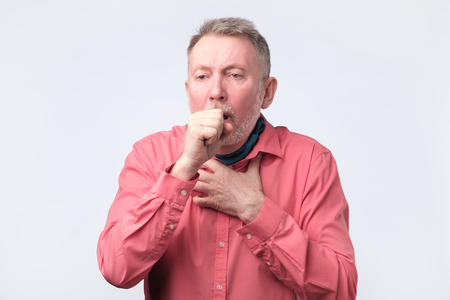 Photo pour European gentleman in red shirt coughing because of pulmonary diseas - image libre de droit