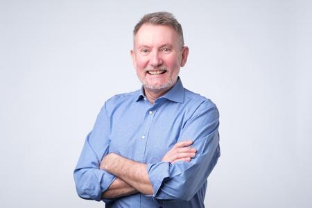 Photo for Senior man in blue shirt smiling broadly - Royalty Free Image