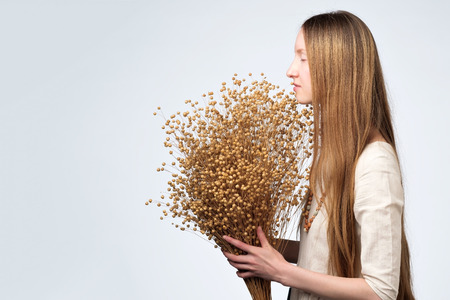 Photo for Dried flowers of flax in the hands of a beautiful girl with lon hair. - Royalty Free Image