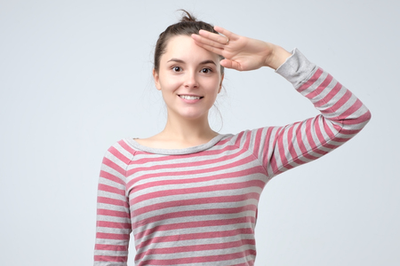 Photo for Young european woman saluting showing her patriotism. Ready to protect her country. - Royalty Free Image